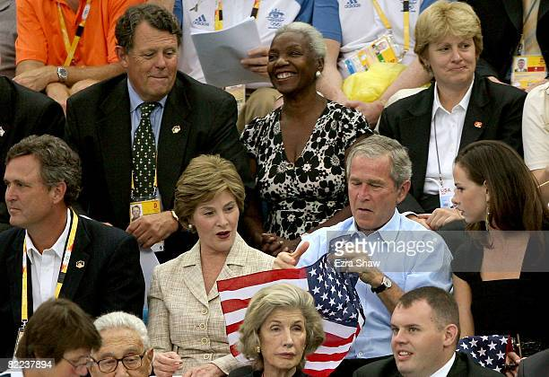 President of the United States George W Bush holds up the American Flag the wrong way before wife Laura Bush instructs him to turn it around while...