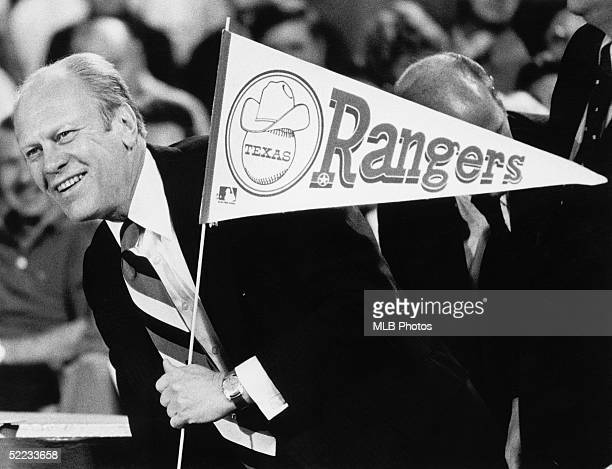 President of the United States Gerald Ford holds a Ranger flag after throwing out the first pitch at the opening game for the 1976 Texas Rangers on...