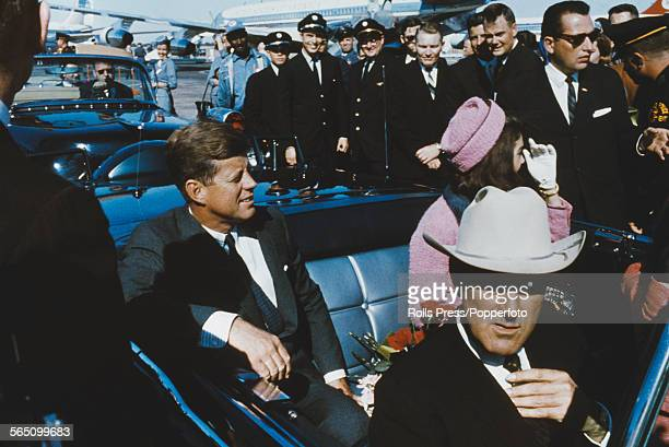 President of the United States John F Kennedy pictured with his wife Jacqueline Kennedy seated in the rear seat of an open top limousine forming part...