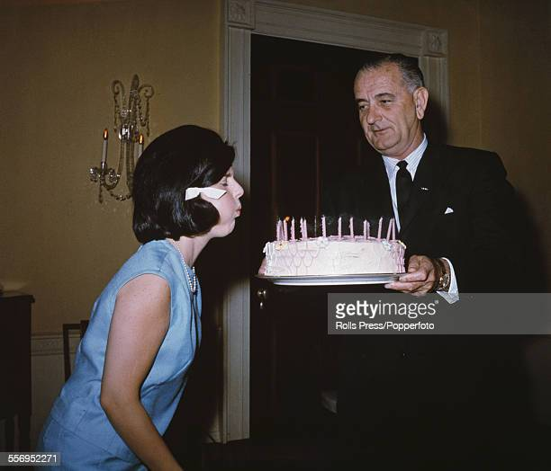 President of the United States Lyndon B Johnson holds a birthday cake in celebration of the 17th birthday of his daughter Luci Baines Johnson as she...