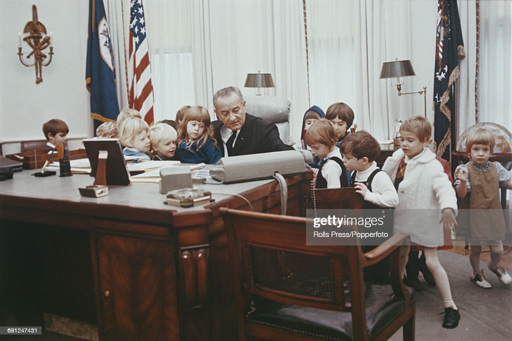 President of the United States, Lyndon B Johnson (1908-1973) pictured sitting at the Johnson desk as he gives a group of young children a tour of the Oval Office in the White House in Washington DC, United States in November 1967.