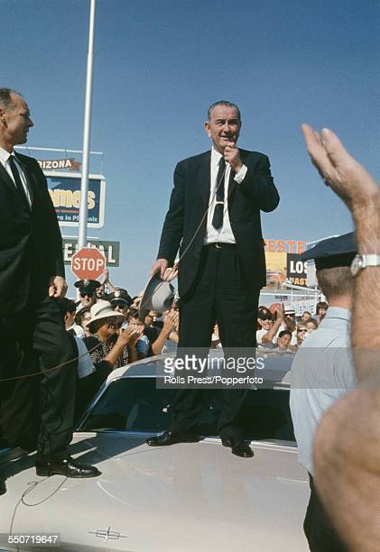 President of the United States Lyndon B Johnson pictured standing on the trunk of a Lincoln car holding a microphone to address supporters and crowds...