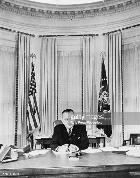President of the United States Lyndon B Johnson sits at his desk in the Oval Office posing for one of his first official photographs following the...