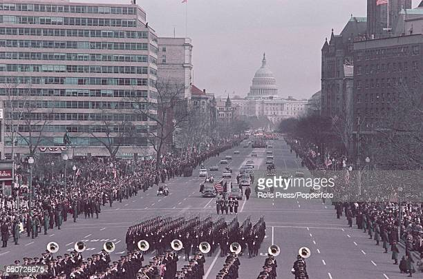 President of the United States Lyndon B Johnson surrounded by Secret Service agents and a military escort rides in a presidential limousine from the...