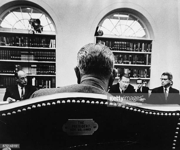 President of the United States Lyndon B Johnson with his back to the camera pictured in conference with United Nations Ambassador Adlai Stevenson...