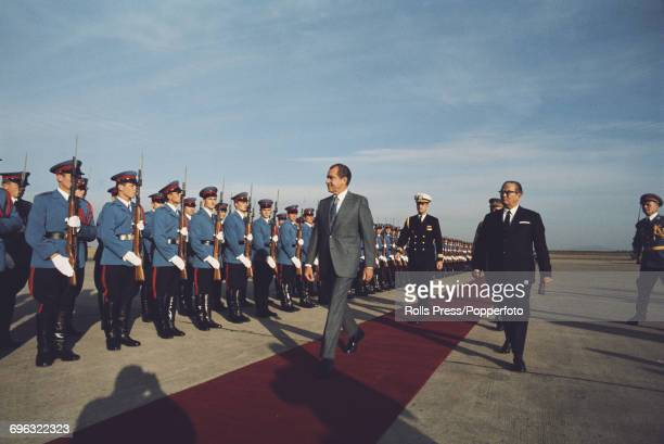 President of the United States Richard Nixon walks along a red carpet with Josip Broz Tito President of Yugoslavia as they inspect the honour guard...