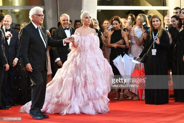 President of the Venice Biennale Paolo Baratta and Festival Director Alberto Barbera greet singer and actress Lady Gaga as she arrives for the...