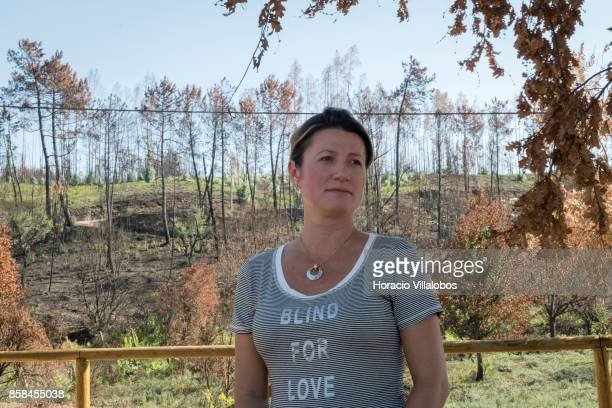 President of the Victims Associacion of Pedrogao Grande Fire Nadia Piazza who lost a child and eight inlaws to the fire stands before trees that are...