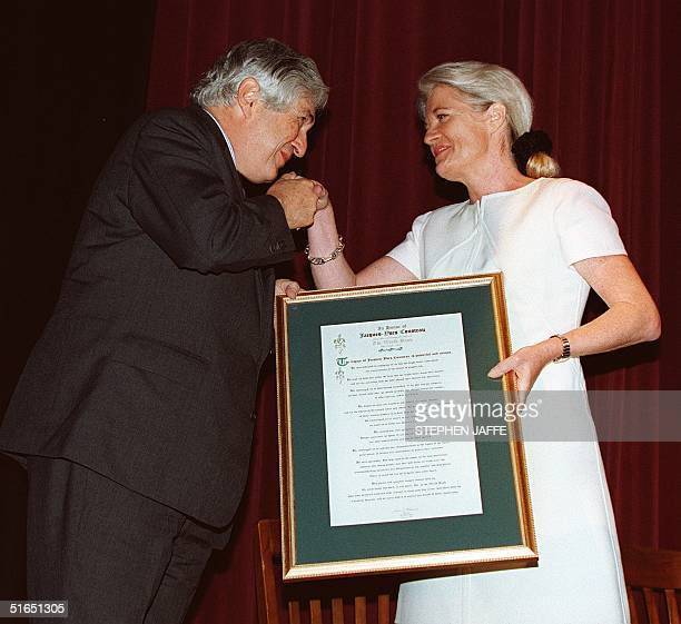 President of the World Bank James Wolfensohn kisses the hand of Francine Cousteau after presenting her with an award in the name of her late husband...