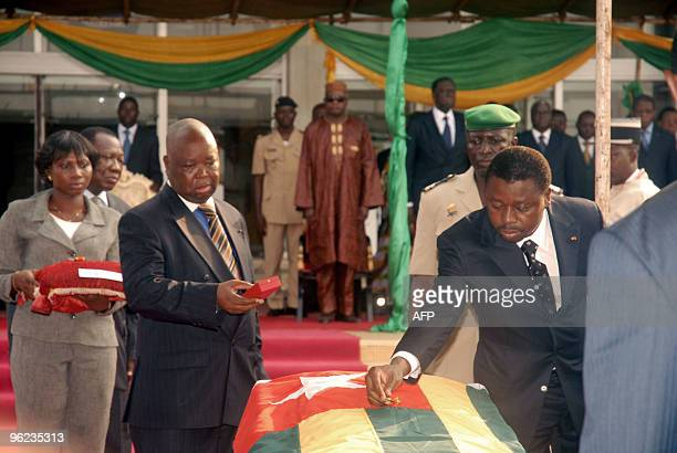 President of Togo Faure Gnassingbe places a posthumous award on the coffin of one of the victims of an attack on the bus carrying the Togo national...