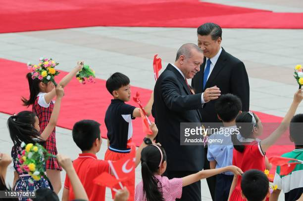 President of Turkey, Recep Tayyip Erdogan , flanked by Chinese President Xi Jinping , greets the children waving flags of Turkey after viewing the...