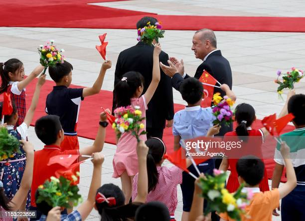 President of Turkey, Recep Tayyip Erdogan , flanked by Chinese President Xi Jinping , greets the children waving flags of Turkey and holding flowers...