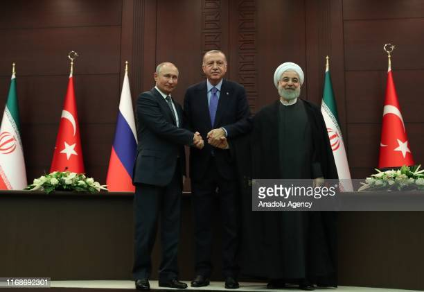 President of Turkey Recep Tayyip Erdogan , President of Russia Vladimir Putin and President of Iran Hassan Rouhani shake hands as they pose for a...