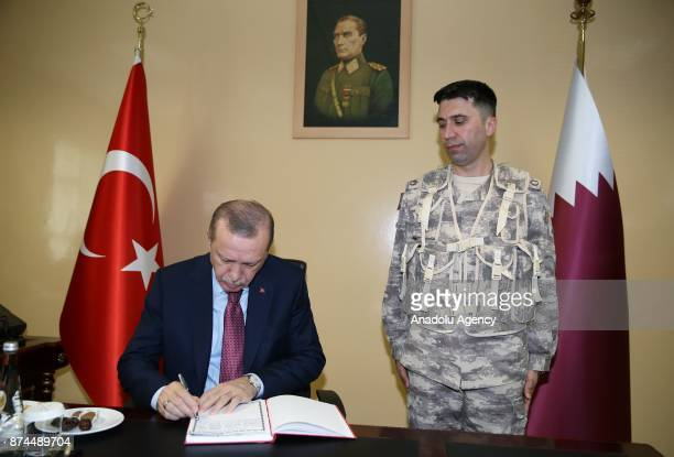 President of Turkey Recep Tayyip Erdogan signs guest book during his visit at the QatariTurkish Armed Forces Land Command base in Doha Qatar on...