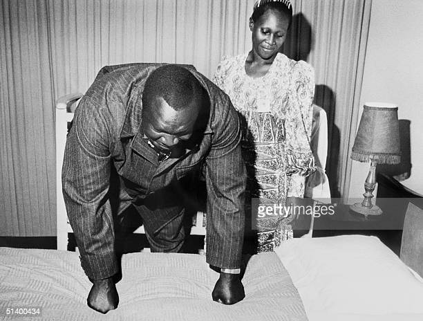 President of Uganda Idi Amin Dada tests the firmness of his bed in July 1975 in Kampala as an unidentified woman looks on His reign of terror lasted...