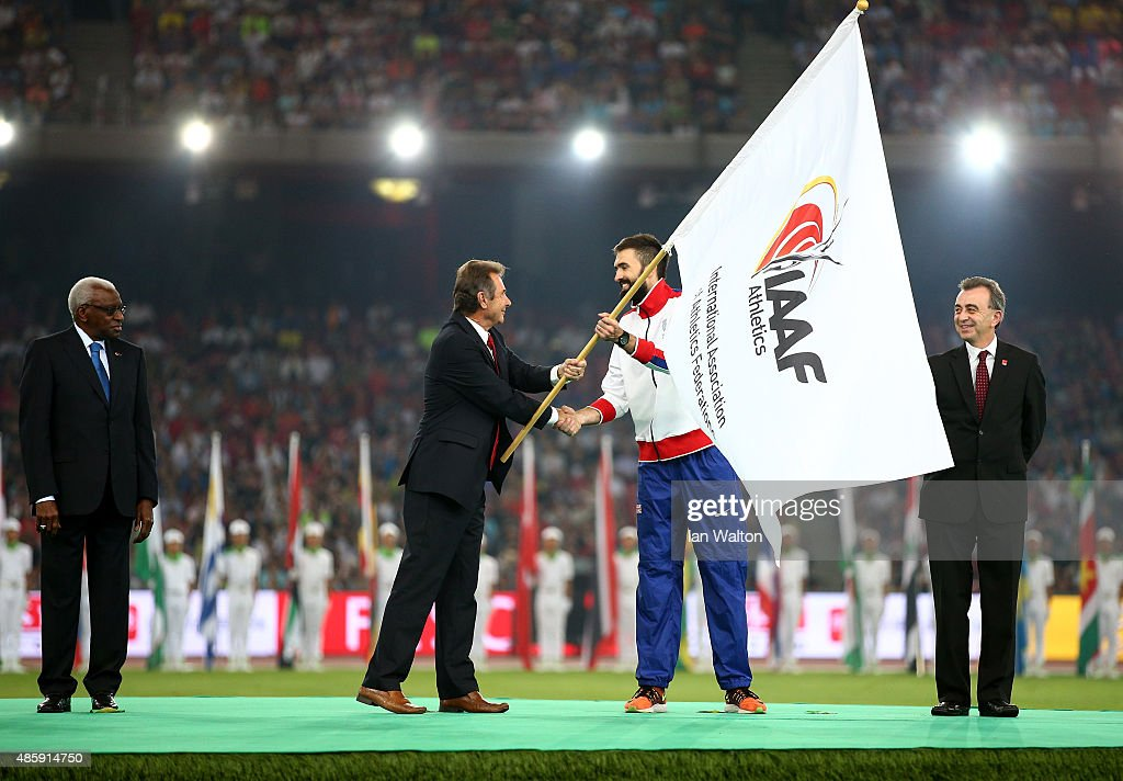 President of UK athletics Lynn Davies hands over the IAAF flag to Martyn Rooney, Captain of Great Britain during the closing ceremony during day nine of the 15th IAAF World Athletics Championships Beijing 2015 at Beijing National Stadium on August 30, 2015 in Beijing, China.