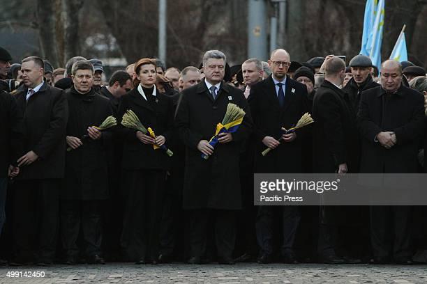 President of Ukraine Petro Poroshenko with his wife Maryna Poroshenko and Prime Minister Arsenii Yatseniuk honor the memory of Holodomor victims by...