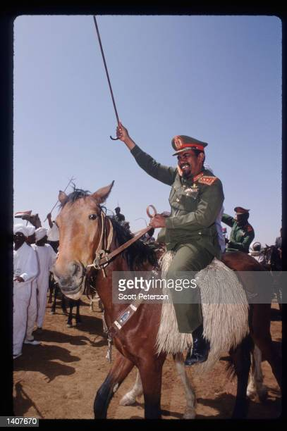 President Omar Hassan el-Bashir rides a horse as Sudanese warriors participate in a rally for him February 28, 1992 in Ed Daein, Sudan. Upon his...
