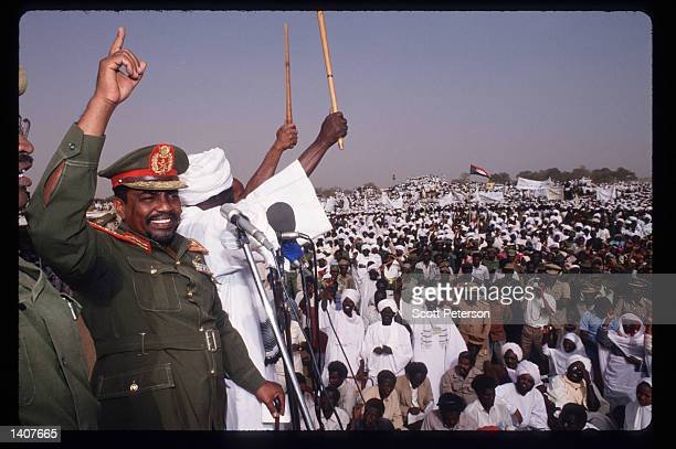 President Omar Hassan el-Bashir speaks as Sudanese warriors participate in a rally for him February 28, 1992 in Ed Daein, Sudan. Upon his return from...