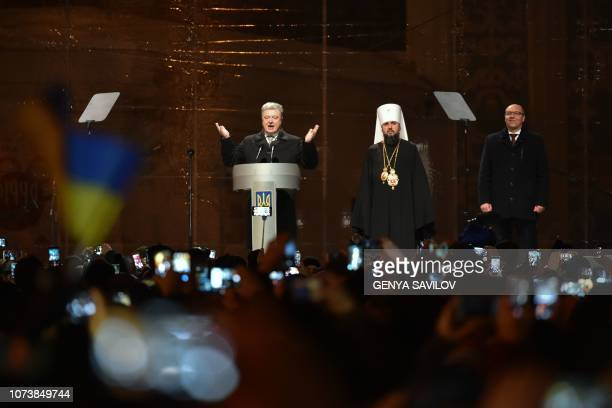President Petro Poroshenko gestures as he delivers a speech next to Yepifaniy the newly elected Primate of the United Church Metropolitan of Kiev and...