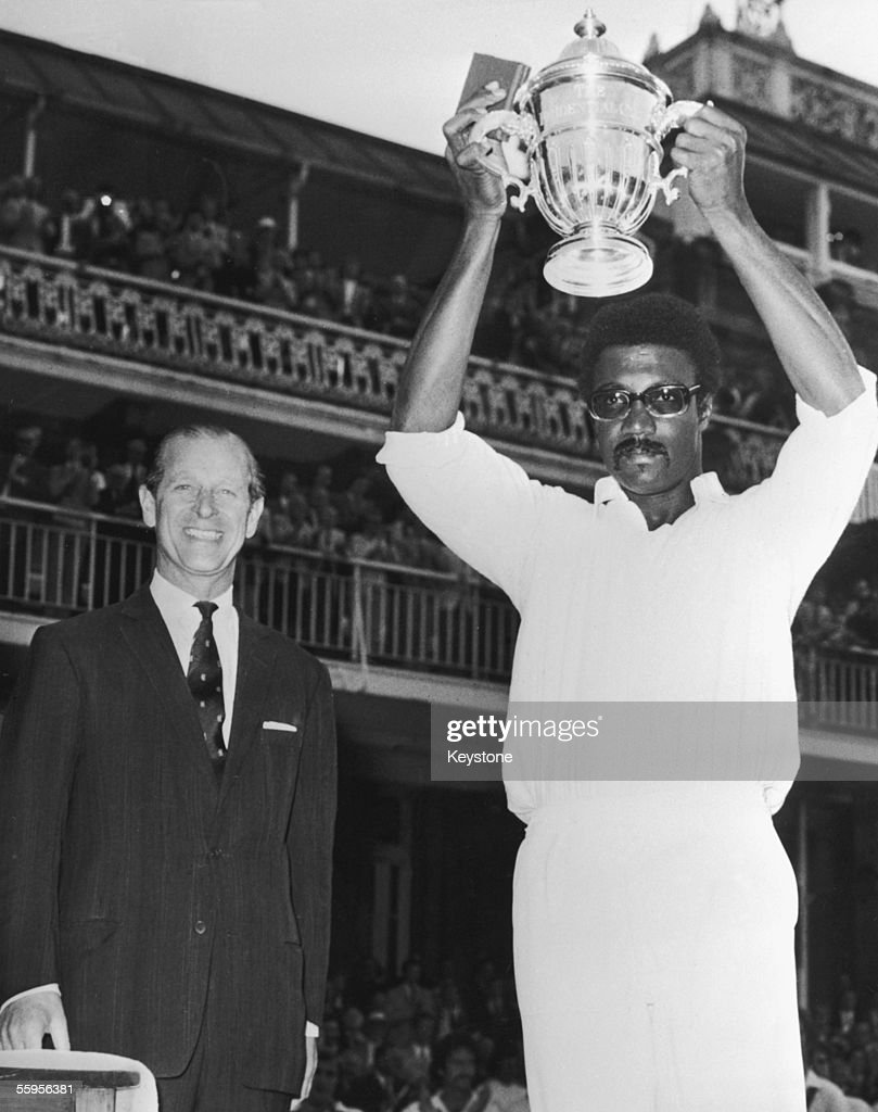 M.C.C. president Prince Philip, Duke of Edinburgh looks on as West Indies captain Clive Lloyd raises the trophy after his team won the final of the Prudential World Cup against Australia, 23rd June 1975.