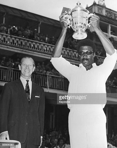 MCC president Prince Philip Duke of Edinburgh looks on as West Indies captain Clive Lloyd raises the trophy after his team won the final of the...