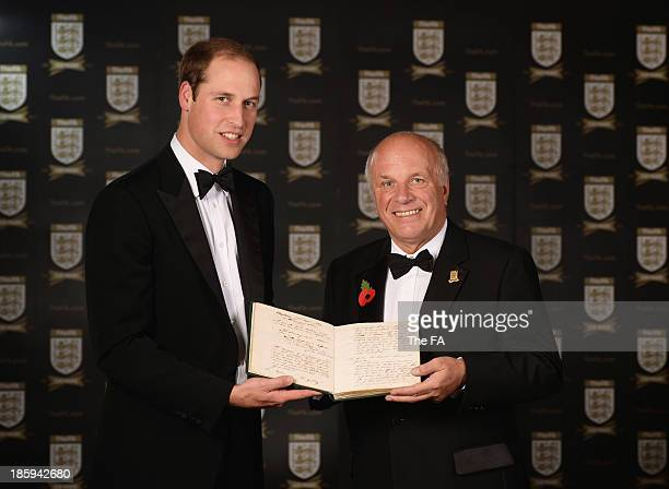 President Prince William, Duke of Cambridge and Greg Dyke, FA Chairman pose with the original FA Minute Book from 1863 featuring the first laws of...