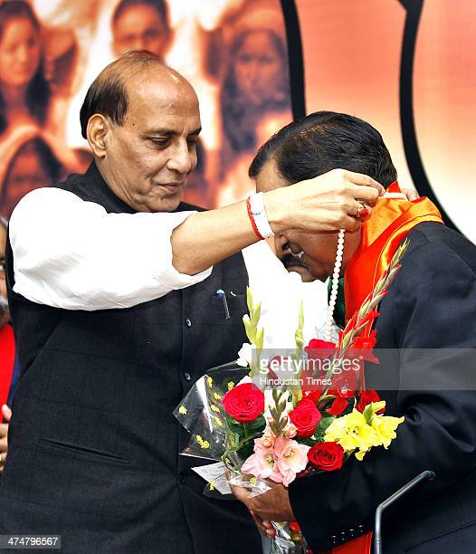 President Rajnath Singh presents a bouquet to former RAW Chief Sanjeev Tripathi who joined the party on February 25 2014 in New Delhi India Tripathi...