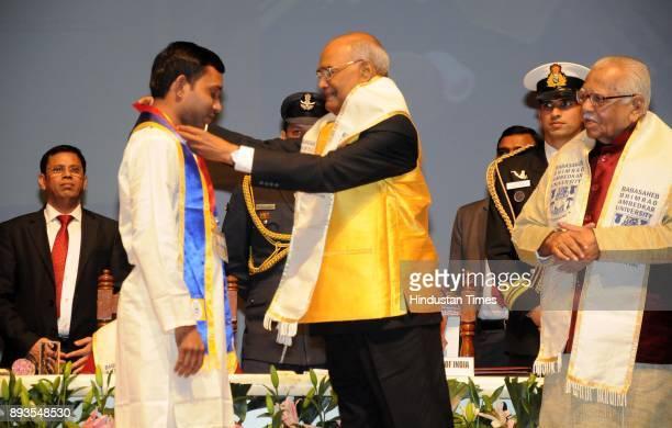 President Ram Nath Kovind giving medal to topper Manjesh Kumar at the 7th convocation of Babasaheb Bhimrao Ambedkar University on December 15 2017 in...