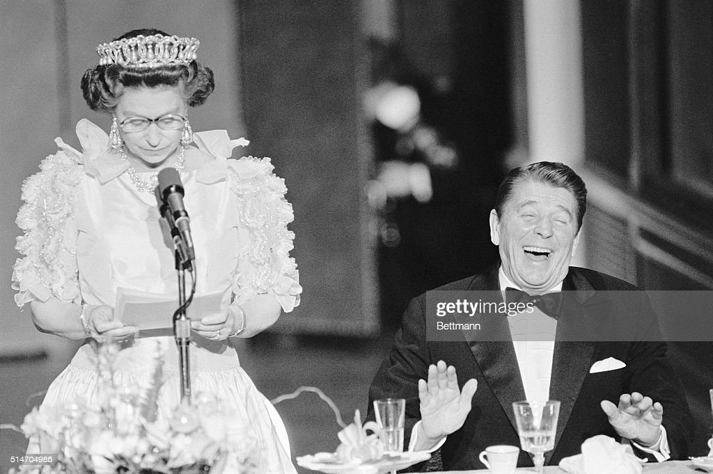 President Reagan laughs following a joke by the straight-faced Queen Elizabeth II, who commented on the lousy California weather she has experienced since her arrival to the States. The British Queen is delivering a brief address during a state dinner held at the De Young Museum in San Francisco.
