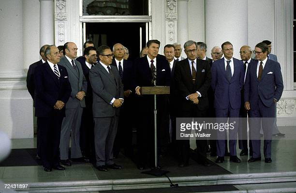 President Reagan makes statement to press as former government officials stand behind him to show their support for sale of AWACS equipped planes to...
