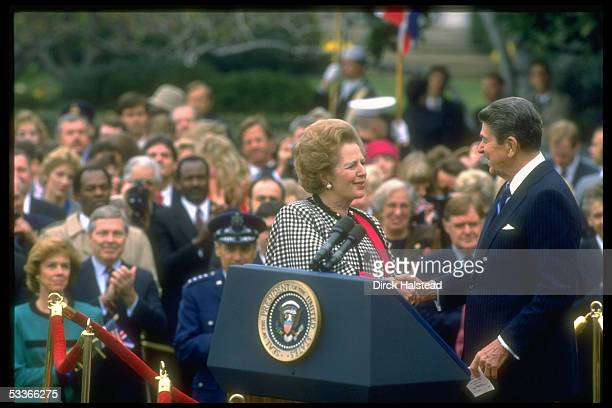 President Reagan shaking hands warmly with British PM Thatcher during ceremony outside at WH poised in front of crowd of dignitaries et al