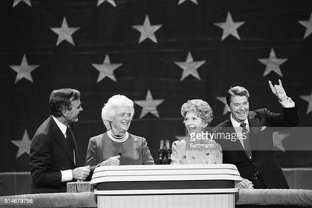 """President Reagan shows a Texas """"hookup horns"""" sign as he is joined by Nancy Reagan, Vice President George Bush, and Barbara Bush at the Republican..."""
