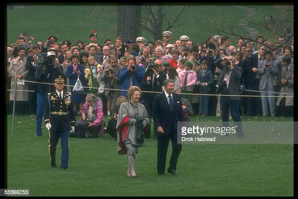 President Reagan with British PM Thatcher walking past knot of fans photographers on WH lawn