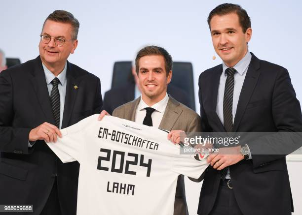 DFB President Reinhard Grindel and Secretary General Friedrich Curtius hand over a jersey reading 'EM Botschafter 2024 Lahm'  to the new DFB...