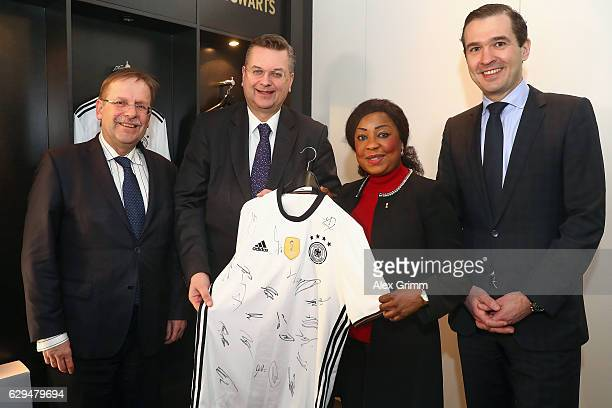 President Reinhard Grindel DFB General Secretary Friedrich Curtius and First DFB Vice President Rainer Koch hand over a signed Die Mannschaft jersey...