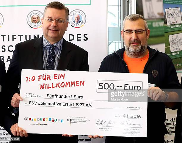 President Reinhard Grindel hands over a cheque to ESC Lokomotive Erfurt prior to day 2 of the 42nd DFB Bundestag at Messe Erfurt on November 4, 2016...