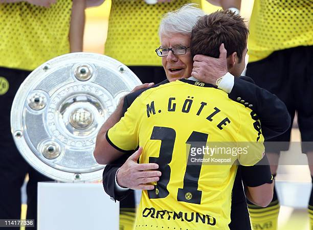 DFL president Reinhard Rauball embraces Mario Goetze of Dortmund after winning the German Championship trophy on the podium to Roman Weidenfeller of...