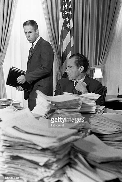 President Richard M Nixon sits behind a mound of papers as he speaks with his chief of staff HR Haldeman in the White House Haldeman was later...