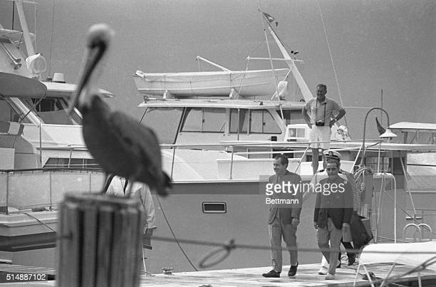 President Richard Nixon and his friend CG 'Bebe' Rebozo walk along a boat ramp at the Key Biscayne Yacht Club under the watchful eyes of a pelican...