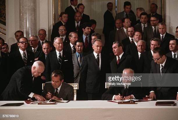 President Richard Nixon and Soviet President Nikolai Podgorny sign a treaty Secretary of State William Rogers stands behind Nixon USSR leader Leonid...