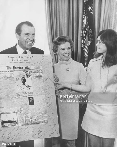 US President Richard Nixon receives a large birthday card from his secretaries Rose Mary Woods and Terry Decker at the White House in Washington DC...