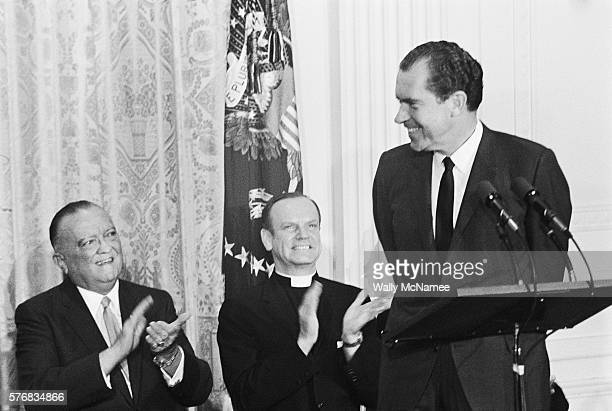 President Richard Nixon receives applause from FBI Director J Edgar Hoover and a clergyman during his speech at the FBI Academy graduation ceremonies