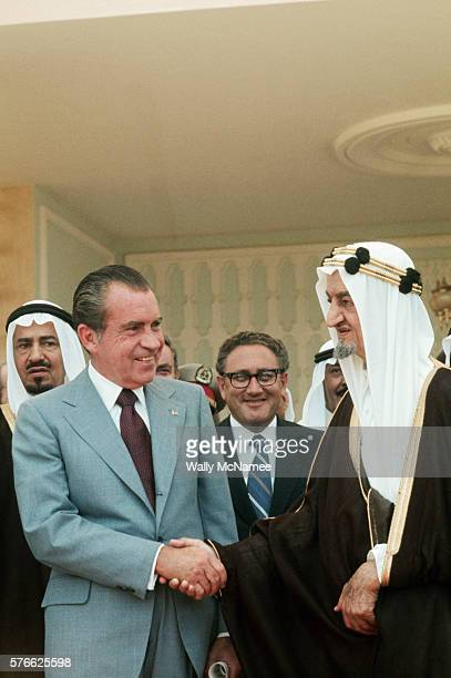 President Richard Nixon shakes hands with King Faisal of Saudi Arabia Henry Kissinger can be seen between them