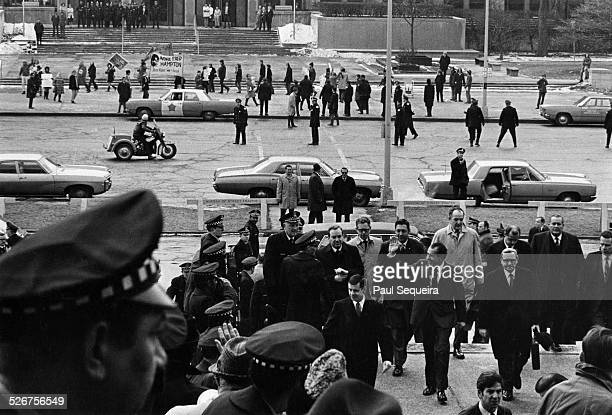 President Richard Nixon surrounded by bodyguards waves as he arrives at the Field Museum Chicago Illinois 1970 In the background a crowd demonstrates...