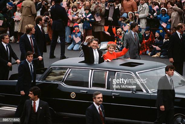 President Ronald Reagan and First Lady Nancy Reagan wave from the sun roof of the presidential limousine during the 1981 inaugural parade down...