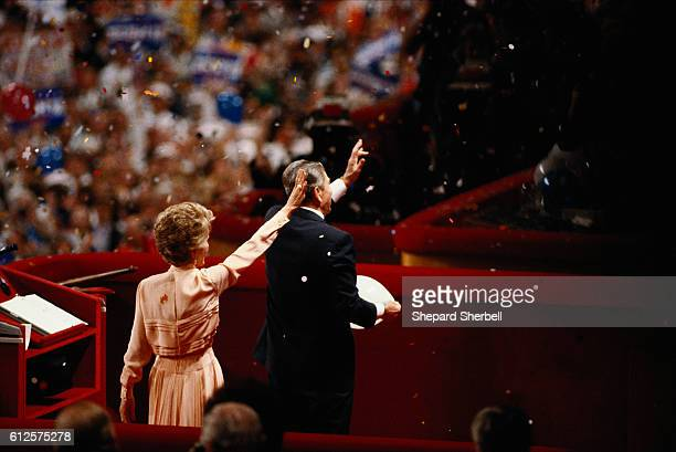 President Ronald Reagan and First Lady Nancy Reagan waving to crowd as confetti falls on them. They are at the 1988 National Republican Convention.