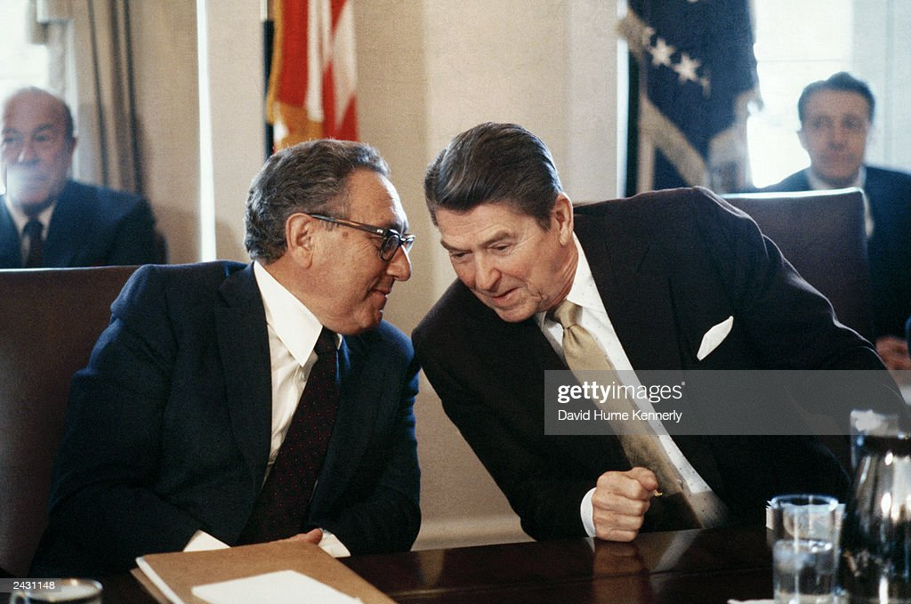 U.S. President Ronald Reagan and former Secretary of State Dr. Henry Kissinger (L) whisper during a meeting in 1983 in Washington, DC. Secretary of State George Schultz (L, rear) and Secretary of Defense Casper Weinberger (R) also attend.