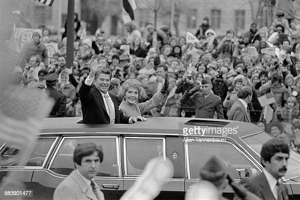 US President Ronald Reagan and his wife First Lady Nancy Reagan wave as they drive down Pennsylvania Avenue to the White House Washington DC January...