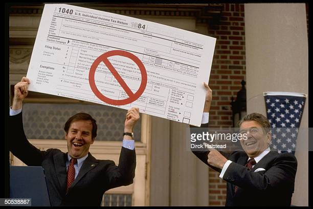 President Ronald Reagan and NJ Governor Thomas Kean holding up giant 1040 income tax form emblazoned with a red circle bisected by a red line during...